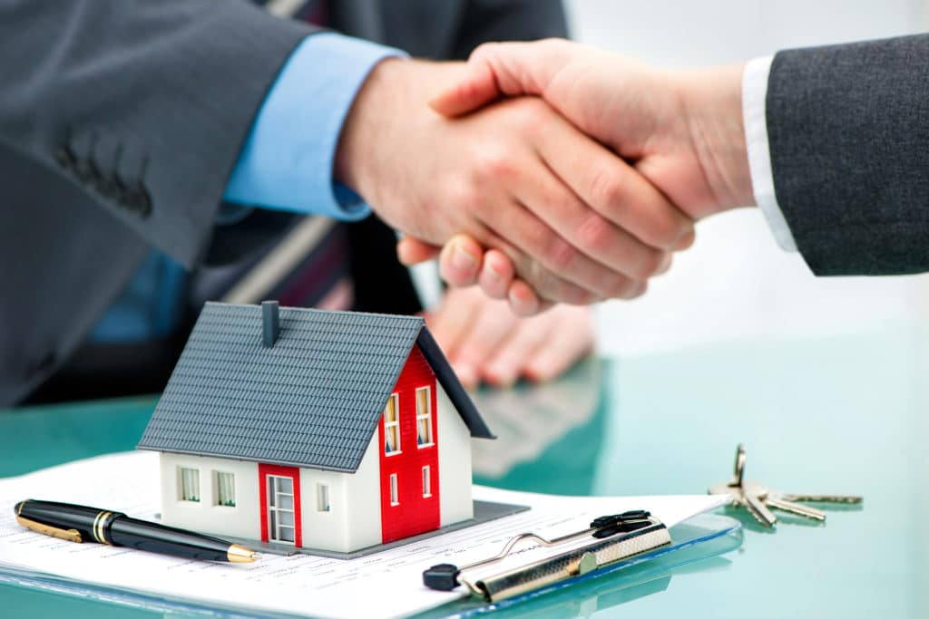 Buyer Agent shaking hands with customer after contract signature