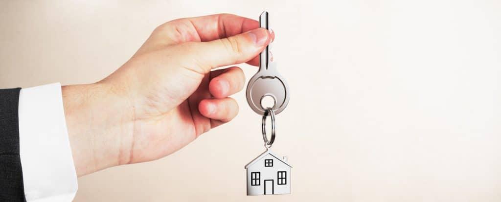 Real estate agent holding keys on light empty interior background