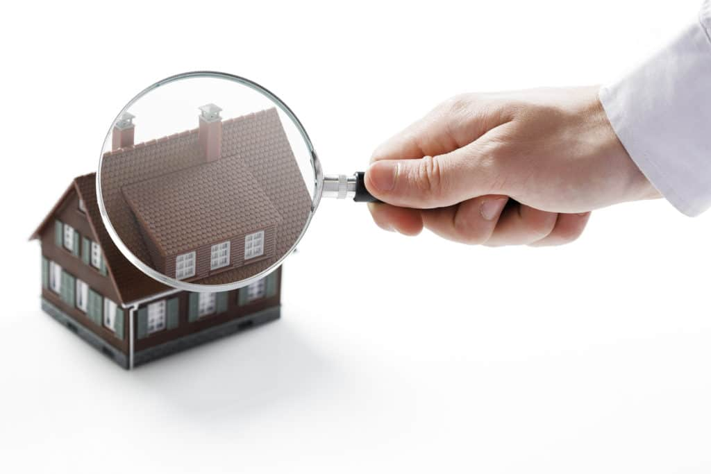 A hand holds a magnifying glass over a miniature house.