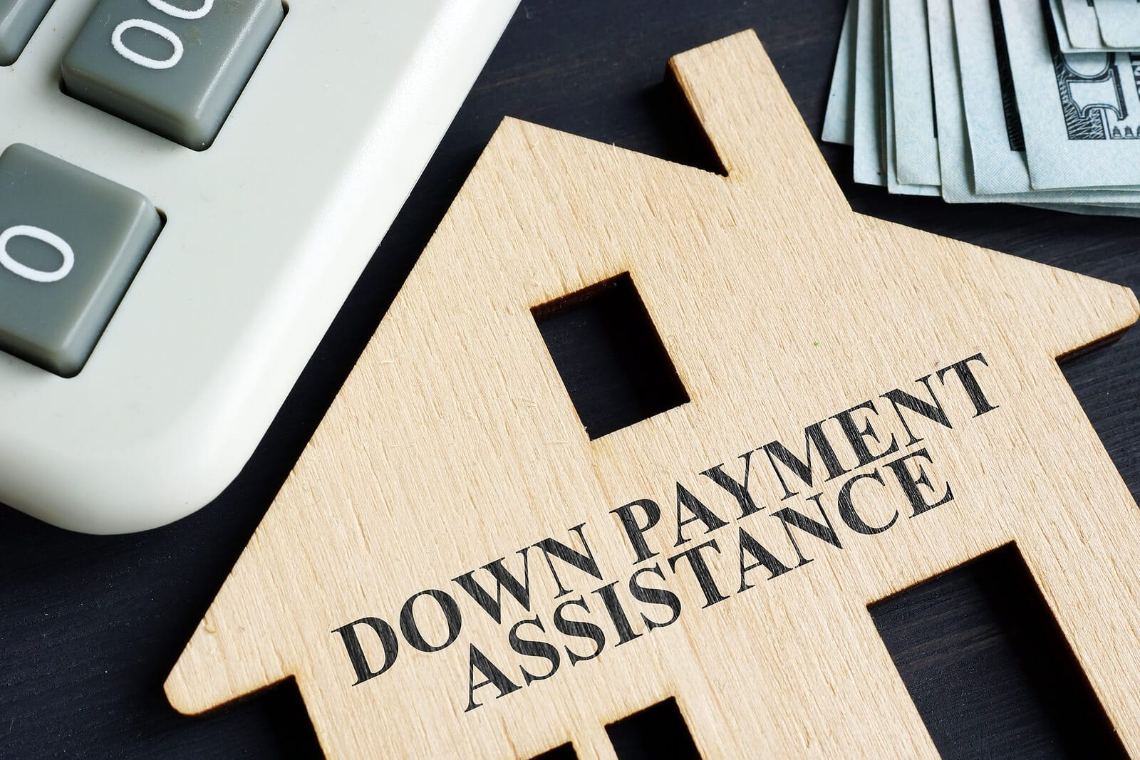 the words down payment assistance etched into a cut out of a house