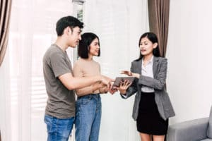 real estate agent and couple walking through a home